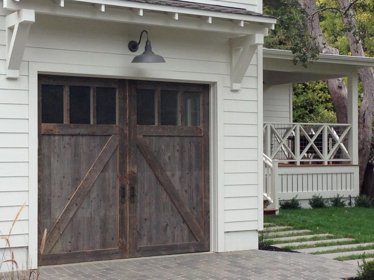 love this entire exterior: Barn wood garage door, light fixture, roof overhang with corbels, X railing on porch with beadboard-like enclosure for underporch in place of the lattice.