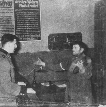 """Foto de um policial alemão interrogando um judeu acusado de tentar """"contrabandear"""" uma fatia de pão para o Gueto de Varsóvia. Varsóvia, Polônia, 1942-1943."""