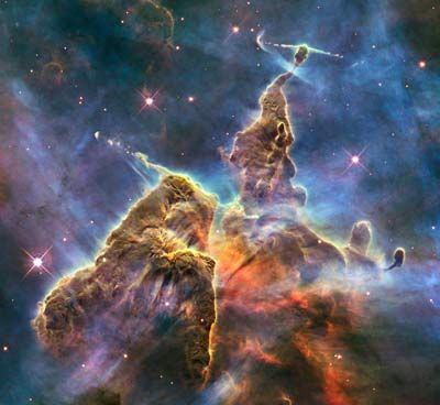 Hubble's 20th anniversary image shows a mountain of dust and gas rising in the Carina Nebula. The top of a three-light-year tall pillar of cool hydrogen is being worn away by the radiation of nearby stars, while stars within the pillar unleash jets of gas that stream from the peaks. It seems unimaginable that things like this exists. It looks so solid, so imposing! It looks unreal!