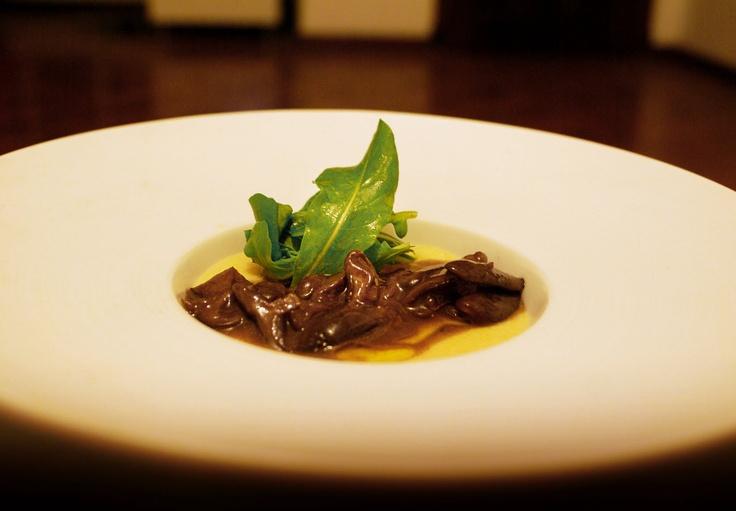 Polenta cremosa com mascarpone, ragu de cogumelos e mini rúcula.