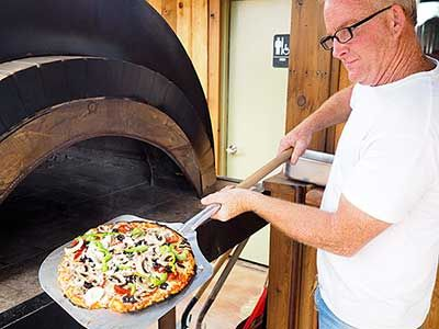 Tommy Scott, owner of Tommy's Mesquite Fired Pizza in Llano, takes out a freshly-cooked pizza from his wood-fired oven. Scott opened the pizzeria about six weeks ago at 312 Bessemer in the Railyard District. It's open 11 a.m.-7 p.m. Tuesday through Saturday. Staff photo by Daniel Clifton