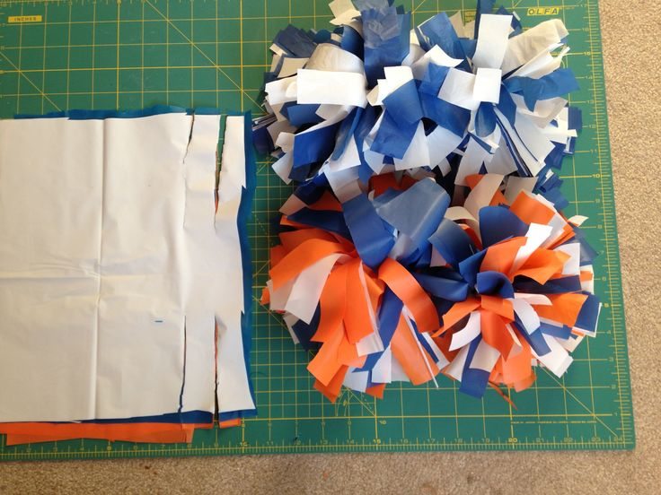 "DIY Cheerleading Pom-Poms:  Easy peasy, buy plastic table cloths( I'd spring for the $1.99 ones at GFS, the dollar store ones are a little thiner, they work though).  Cut  plastic into 9""x12"" rectangles(about 20-30 sheets total.For multiple colors just layer every two), then cut long ways 4.5"" on both sides about every inch or so, the center remains uncut, gather the center and tape tightly with duck table or electrical tape.  Then fluff it by pulling in opposite directions and scrunching."