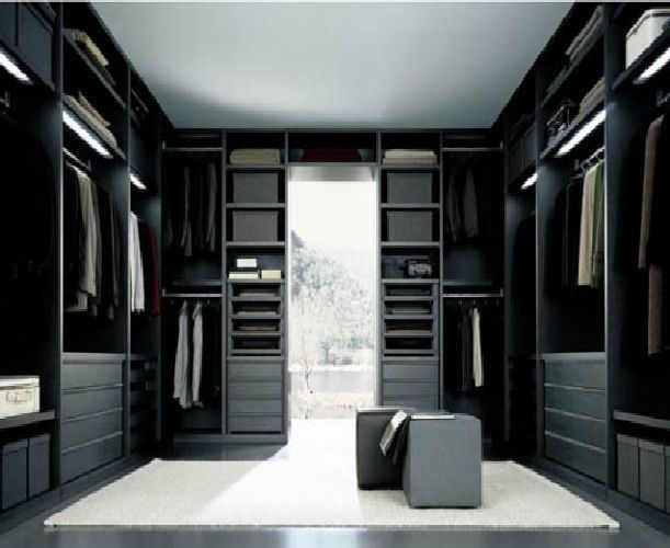Sleek modern walk-in closet design with custom cabinetry & ottoman seats