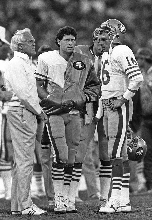 Bill Walsh, Steve Young (center) and Joe Montana stand on the sidelines of a 1987 preseason game -- just a few months after Walsh brought Young to the 49ers. (Associated Press)