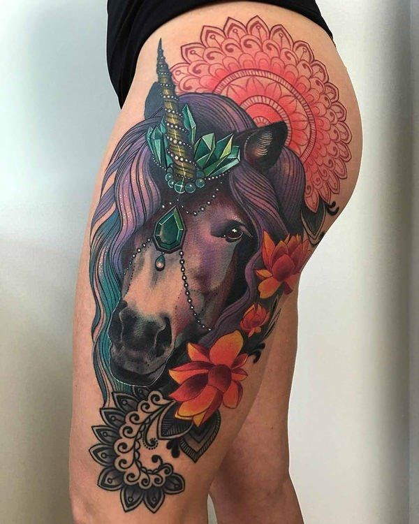 Very detailed unicorn tattoo on the thighs. The striking colors that the design has is absolutely well details and beautiful. You can see the unicorn adorned with jewels and flowers.