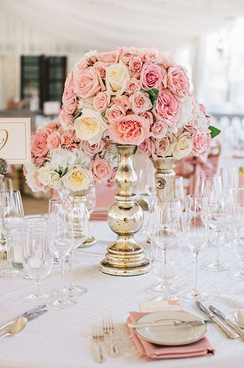 Add intrigue by using floral vessels in varying heights filled with blush and cream roses.