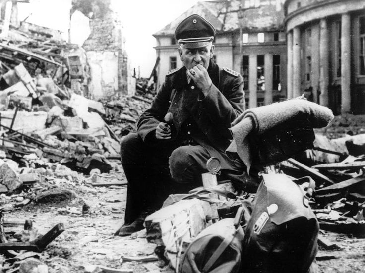 A German officer eats C-rations as he sits amid the ruins of Saarbrücken a German city and stronghold along the Siegfried Line in early spring of 1945. [900x674]