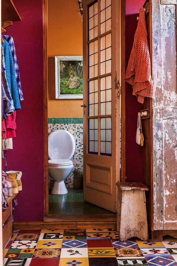 Baño colorido con pared naranja y venecitas verdes.