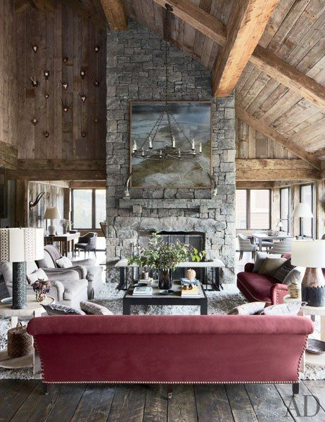 A rustic Montana mountain retreat's living room features a rough-hewn timber ceiling.
