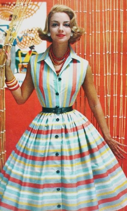 July 1958.  A cute A-line sleeveless dress with cinched waist in this nifty blue with red & yellow stripes.  Date night redux.