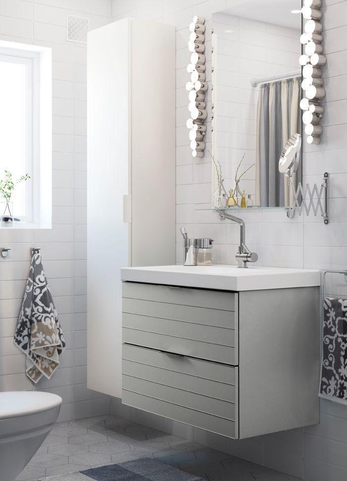 Bílá malá koupelna s bílou vysokou skříňkou, zrcadlem a šedou skříňkou pod umyvadlo se 2 zásuvkami