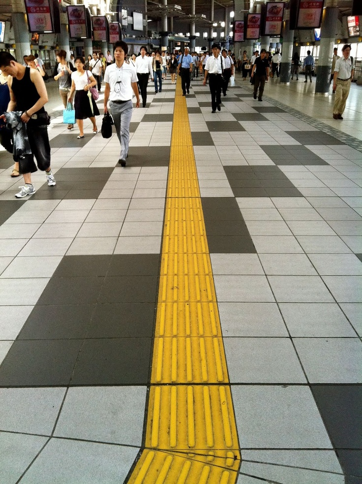 In Japan,yellow raised grooved lines on sidewalks are a form of street braille to help the blind. Yellow lines are in all train station, no exceptions, and on major roads and small streets. Yellow tiles with linear ridges mean:  walk in a straight line. Tiles with round bumps mean: turns, traffic intersections, stairs, etc. Traffic intersections have audio cues indicating when it's safe to cross.