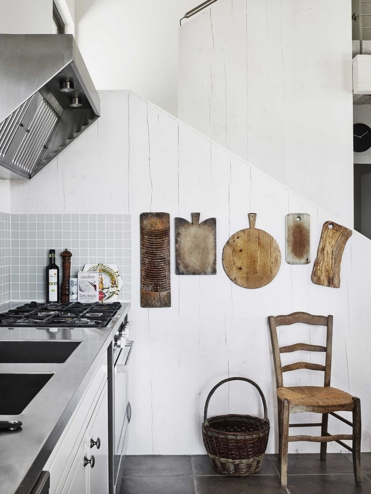 Rustic and industrial kitchen with wooden cutting boards and a gas cooker.