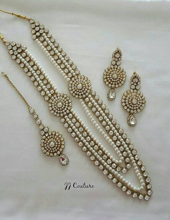 Beautifully handcrafted designer Pearl and Gold Kundan Jewelry Set.  Necklace is designed with gold chains filled with clear rhinestones and pearl chains. To give a finishing touch the necklace is adorned with shiny clear rhinestones.  Set comes with matching earrings and tikka in clear rhinestones on a gold metal base. The perfect statement piece for a bride for her wedding day or for any occasion.  If you have any questions, please message me.  Thank you
