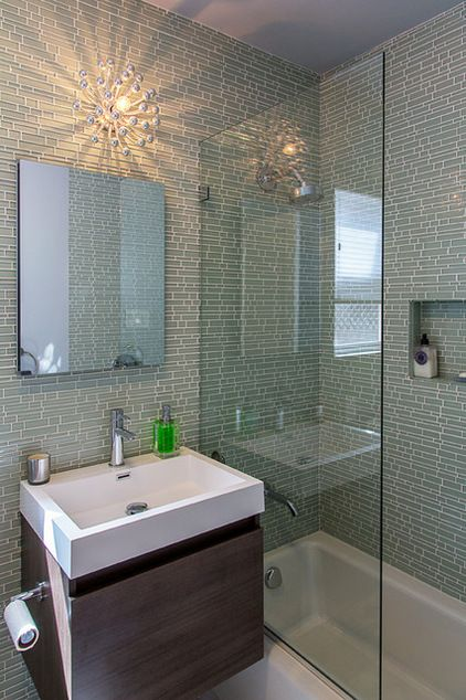 """Light colors, reflective tiles and an anemone-like sconce lighten the space in the master bath, while a floating vanity and clear glass shower stall make the room feel larger. They added a contemporary touch with rectilinear green glass tiles. """"We settled on translucent tiles to not only avoid overpowering the room, but to create a fluid environment inspired by the sea,"""" Asher says.  Houzz"""