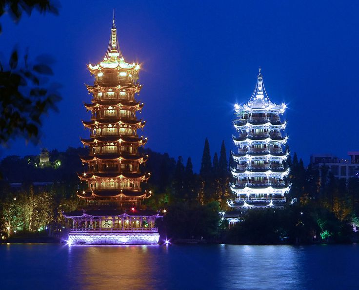 https://flic.kr/p/oNDJ3E | Moon & Sun | Elegantly embellishing the scenery of Shān Lake (杉湖; Shān Hú), the Sun and Moon Twin Pagodas, beautifully illuminated at night, are the highlight of a stroll around Guìlín's two central lakes. The octagonal, seven-storey Moon Pagoda (月塔; Yuè Tǎ) is connected by an underwater tunnel to the 41m-high Sun Pagoda (日塔; Rì Tǎ), the world's tallest copper pagoda and one of the few pagodas anywhere in the world with a lift.