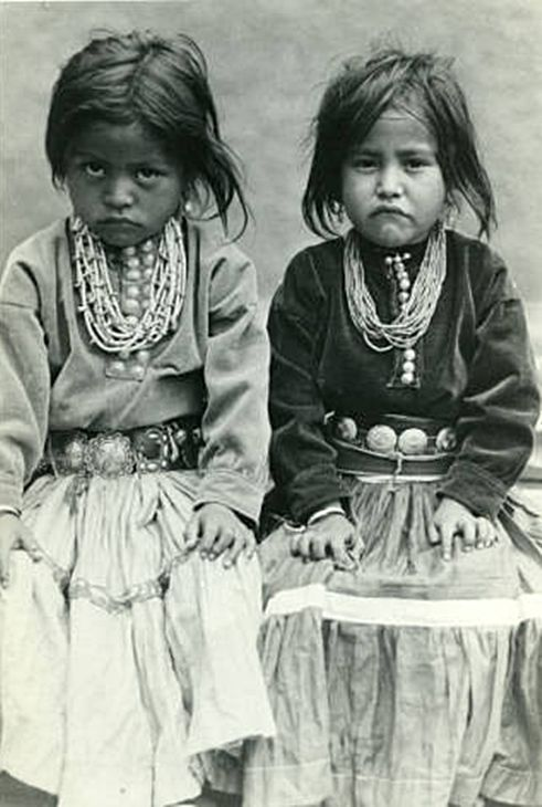 """""""Two Navajo Girls,"""" Two preschool age Navajo girls sitting next to each other. Both are wearing velvet like tops and long gathered, tiered skirts. They both are wearing beaded necklaces of several strands and a concho belt. The girls both look unhappy."""