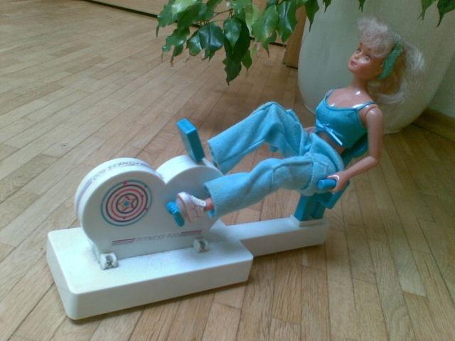 Barbie Ergometer Heimtrainer mit Funktion Sound und Sprache incl. Tolles Ergometer mit Funktion!!  Setzt man die Puppe auf den Sitz, befestigt die Füße an den Pedalen und drückt man auf den Knopf auf der Anzeigentafel, so fängt die Puppe auf dem Ergometer zu trainieren an, wobei eine Musik unterspielte Stimme dazu ertönt, die wiederholend sagt: one, two, three, four.  Die Puppe gehört dazu und ist speziell für das Ergometer bestimmt. Höhe mit Puppe ca. 21 cm, Breite ca. 8 cm, Länge ca. 25…