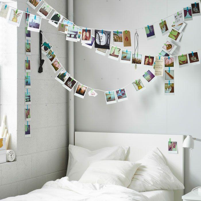 Fotos und Postkarten, an Schnüren quer durch den Raum über einem Bett hängend.