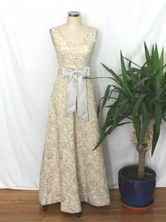 Schitterende jaren 60 avondjurk met verhoogde gouden bloemenpatroon met bleke blauw geborduurde detail op een crème gekleurde stof. Grote bleke blauw satijn sjerp met grote strik aan de taille. Brede v-hals in voor- en achterkant. Metalen rits over rug. Zou een mooie jurk voor de bruid van een winter.  ➸ ➸ M E EEN S U R E M E N T S ➸ ➸ BUST: 34 TAILLE: 26 HEUPEN: 38 LENGTE: 55 1/2  alle metingen, met uitzondering van lengte, zijn genomen vlak en vervolgens verdubbeld *** Alstublieft…