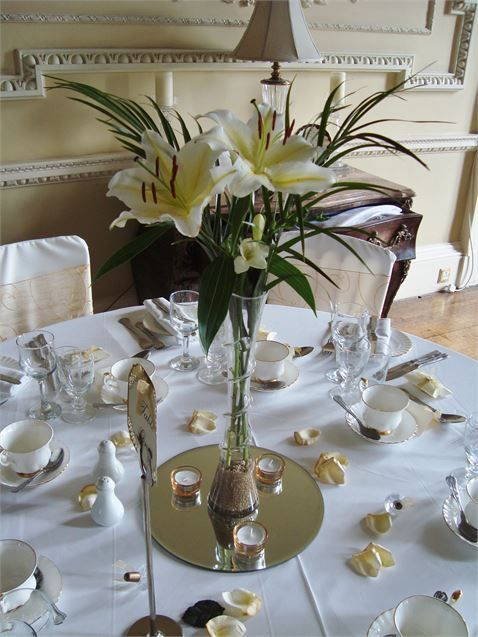 40cm swirled glass lily vase with beautiful white lillies, white freesia and palm leaves set in decorative gold sand and placed on a mirror plate.