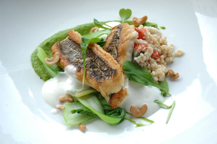 Black Bass With herbed pea puree, cauliflower foam, cous cous, goats cheese, macadamia nut, and bok choi