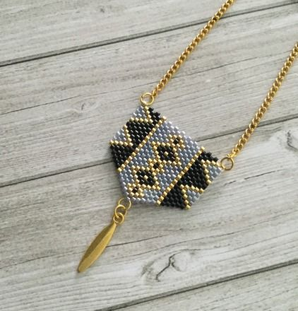 Joli sautoir pendentif tissé en perles miyuki delicas une à une graçe à la technique peyote et breloque ovale en métal doré.  * composées de :                             - 20595666