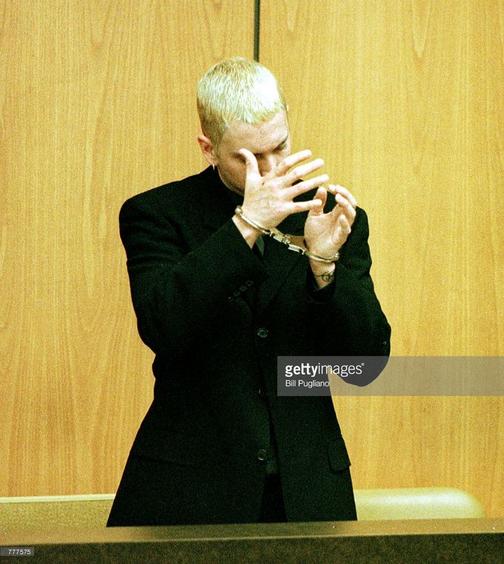 Rap artist Marshall Mathers III, a.k.a. Eminem, left, stands handcuffed June 7, 2000 in the 37th district court in Warren, Michigan during his arraignment on charges of felonious assault and carrying a concealed weapon.