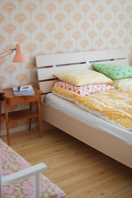 peach wallpaper and colorful bedding