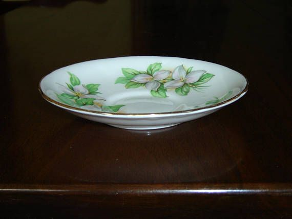 """**** Inventory Clearout ****    Saucer in pattern White Trillium (white flower, green leaves), gold banding on the edges  This saucer measures 5 9/16"""" (14.1 cm) in diameter  Made of bone china from England by Royal Stafford  This saucer is in very good condition    This item has no nicks, chips, cracks, or signs of repair 