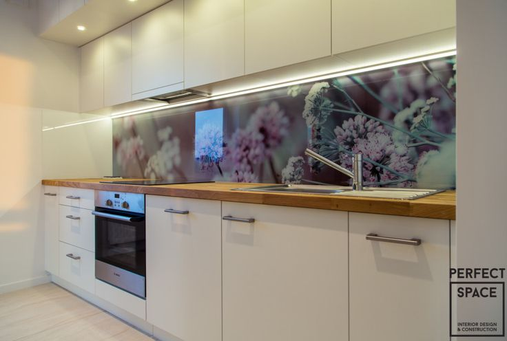 Backsplash z motywem kwiatowym w aranżacji kuchni. Białe szafki oraz drewniany blat idealnie komponują się z kwiatowym backsplashem.