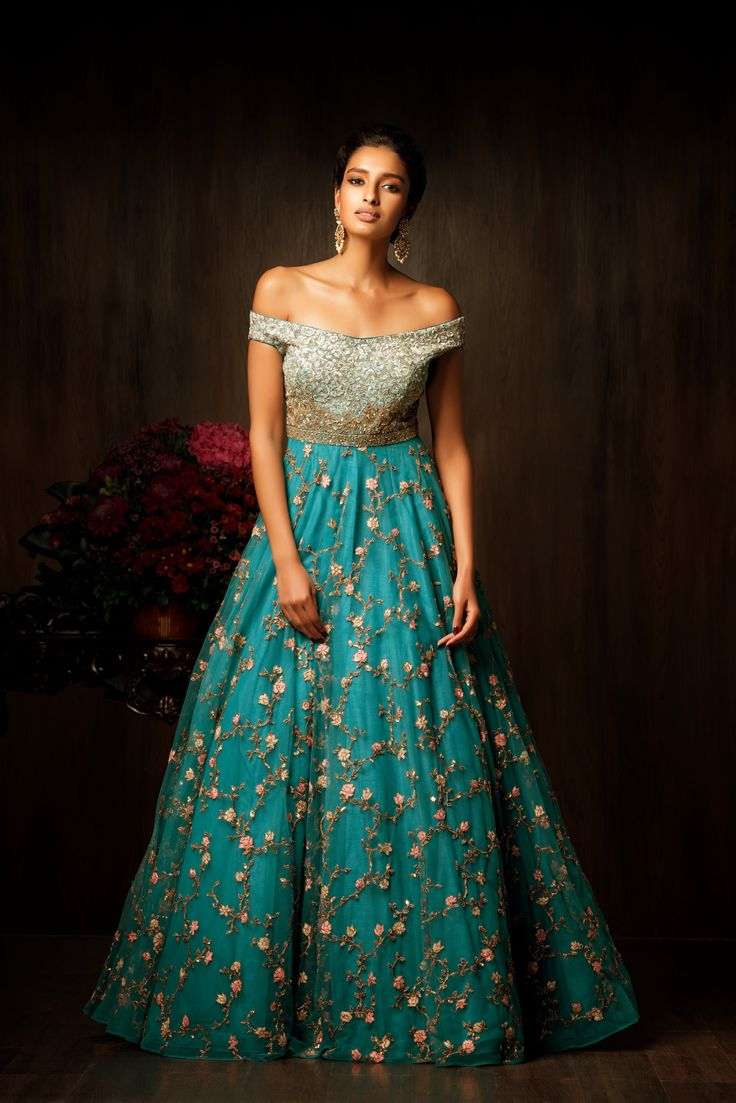 A truly magnificent pagoda blue gown, with an off shoulder bodice which is entirely done in resham thread gradation, with a spray of antique gold tikkis and pearls. The tulle skirt has a full flare and is ornamented with an antique peeta jaal and resham thread flowers. The delicate jaal on the skirt and the rich bodice makes this gown fit for reception, sangeet and cocktail parties. #bridal #trends #bridal2017 #bridalfashion #bridaldress #weddinglehenga #sangeetlook #bridesmaid #outifts