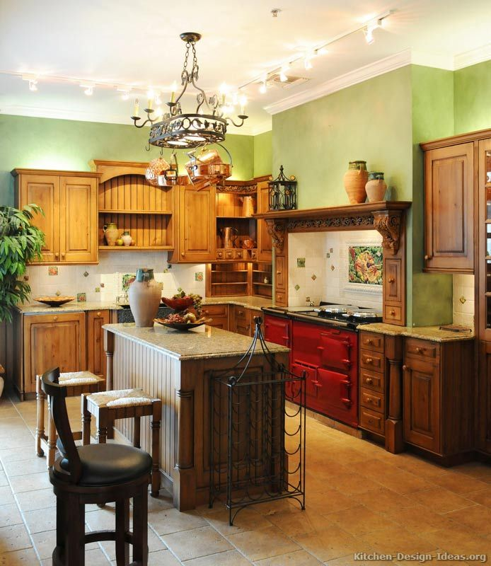 #Kitchen Idea of the Day: Color me hungry: Golden-brown kitchen with red AGA range, green walls, travertine tile floors. LOVE.
