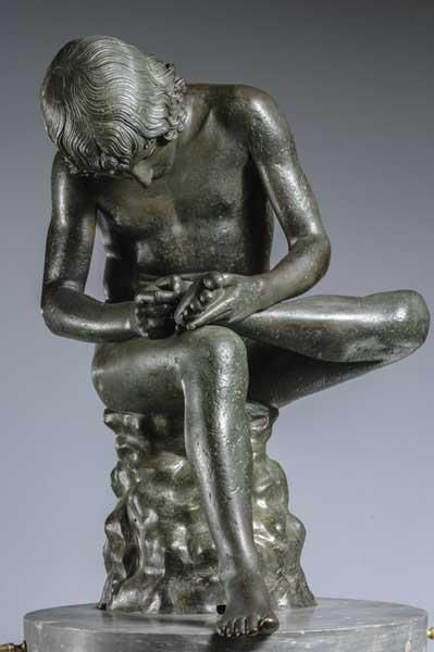 """""""Spinario"""" (""""Thorn-picker""""), a Late Republican bronze statue representing a pastiche of contrasting styles: the stiff Severe/Archaic head (early 5th century BC) is attached to a fluid Hellenistic body (3rd-1st centuries BC)."""