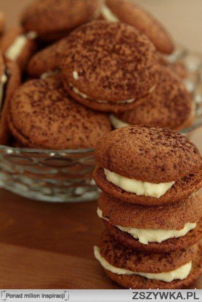 Ciasteczka Tiramisu Składniki na 30 ciastek: 5 dużych jajek (osobno białka i żółtka) 1 szklanka cukru 3 łyżki kawy rozpuszczalnej pół szklanki mąki  1/4 łyżeczki soli kakao do oprószenia - około 2 łyżek  Składniki na krem: 3/4 szklanki serka mascarpone 1/4 szklanki cukru pudru 3 łyżki likieru migdałowego np. amaretto  pół łyżeczki ekstraktu z wanilii Ponadto: 170 g czekolady deserowej  Używając miksera z przysadką do ubijania białek ubić żółtka z połową cukru do białości (około 3 minuty)…