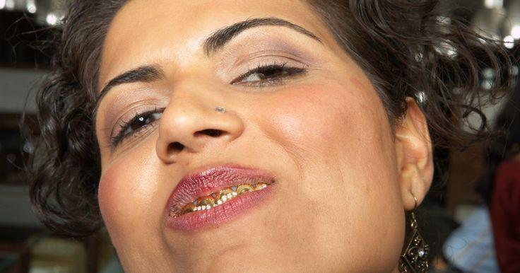 """Como fazer dentes de ouro com papel alumínio dourado. Os dentes de ouro usados por artistas e celebridades ricas são um símbolo de status feitos em um processo de várias etapas. Dentistas ou ortodontistas os fazem tirando impressões da boca da pessoa, criando um molde, despejando ouro derretido dentro dele e deixando que o metal esfrie antes de remover o novo conjunto de """"dentes."""" Faça dentes de ouro ..."""