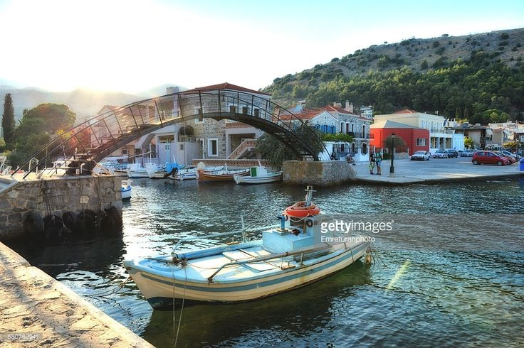 Anchored wooden fishing boat in front of pedestrian bridge at sunset in Lakgada,chios.