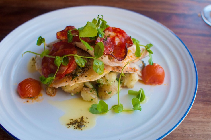 Sea bass fillets oven baked with chorizo and vine-ripe tomatoes, over crushed baby potatoes