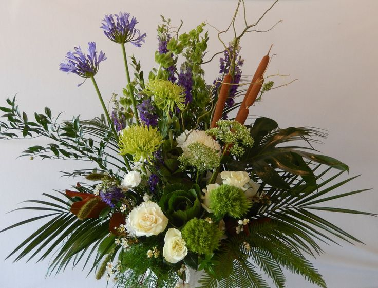 A weekly Lobby arrangement by Dizennio Floral Boutique-Vaughan. This piece uses lots of green and cream tones broken up by the rich blue of the Agapanthus and Cat's Tails giving a seasonal flavour to this arrangement !