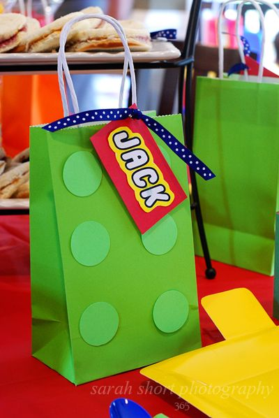 Simple favor bags for your Lego party. Solid paper bags with paper circles adhered to the front. Add a tag and some ribbon for a fun Lego party favor guests can take home with them