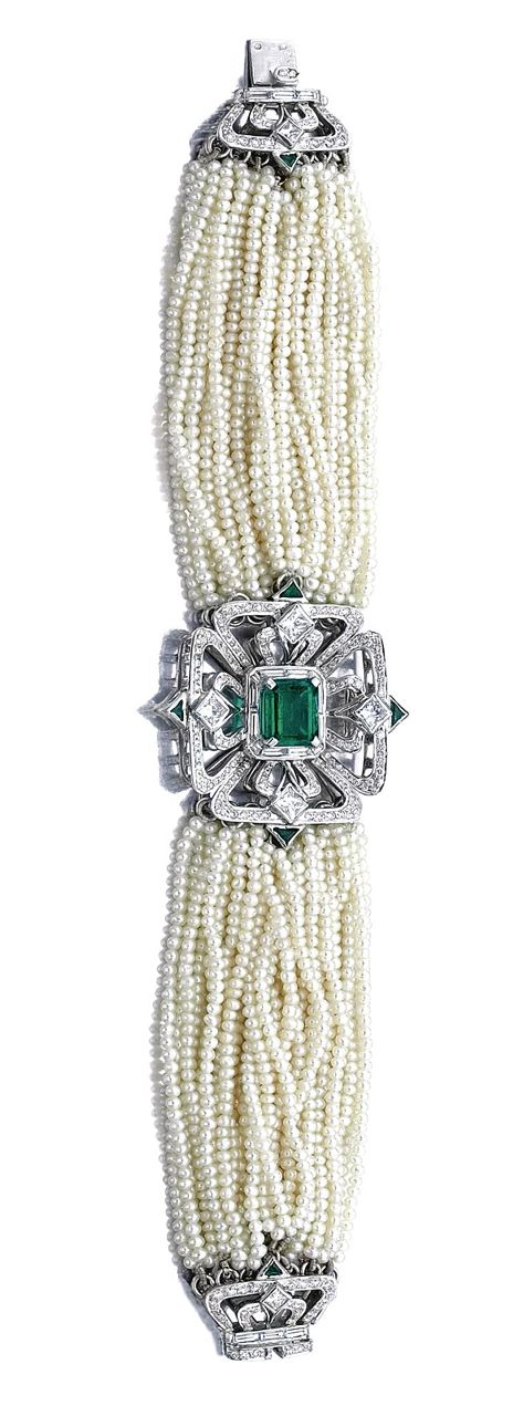 SEED PEARL, EMERALD AND DIAMOND BRACELET, NAROTAMDAS BHAU.  Centring on a stylised open work four clover leaf plaque, set with a step-cut emerald surrounded by princess-, brilliant-cut and baguette diamonds, the straps composed of thirty-four rows of seed pearls, mounted in white gold, length approximately 185mm, signed NB.