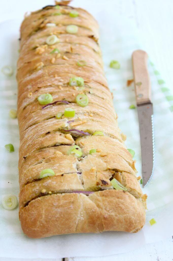 Verwarm je oven voor op 220 graden. Snijd de ciabatta in plakjes van ongeveer 1-2 cm dik. Snijd de plakjes niet helemaal door tot beneden. Het brood moet aan de onderkant aan elkaar vast blijven zitten. Snijd de rode ui in halve ringen en snijd de mozzarella in kleine stukjes. Smeer de pesto tussen de plakjes ciabatta. Verdeel vervolgens de rode ui en de mozzarella ook tussen de plakjes brood. Zet de ciabatta voor circa 12 tot 14 minuten in de oven.