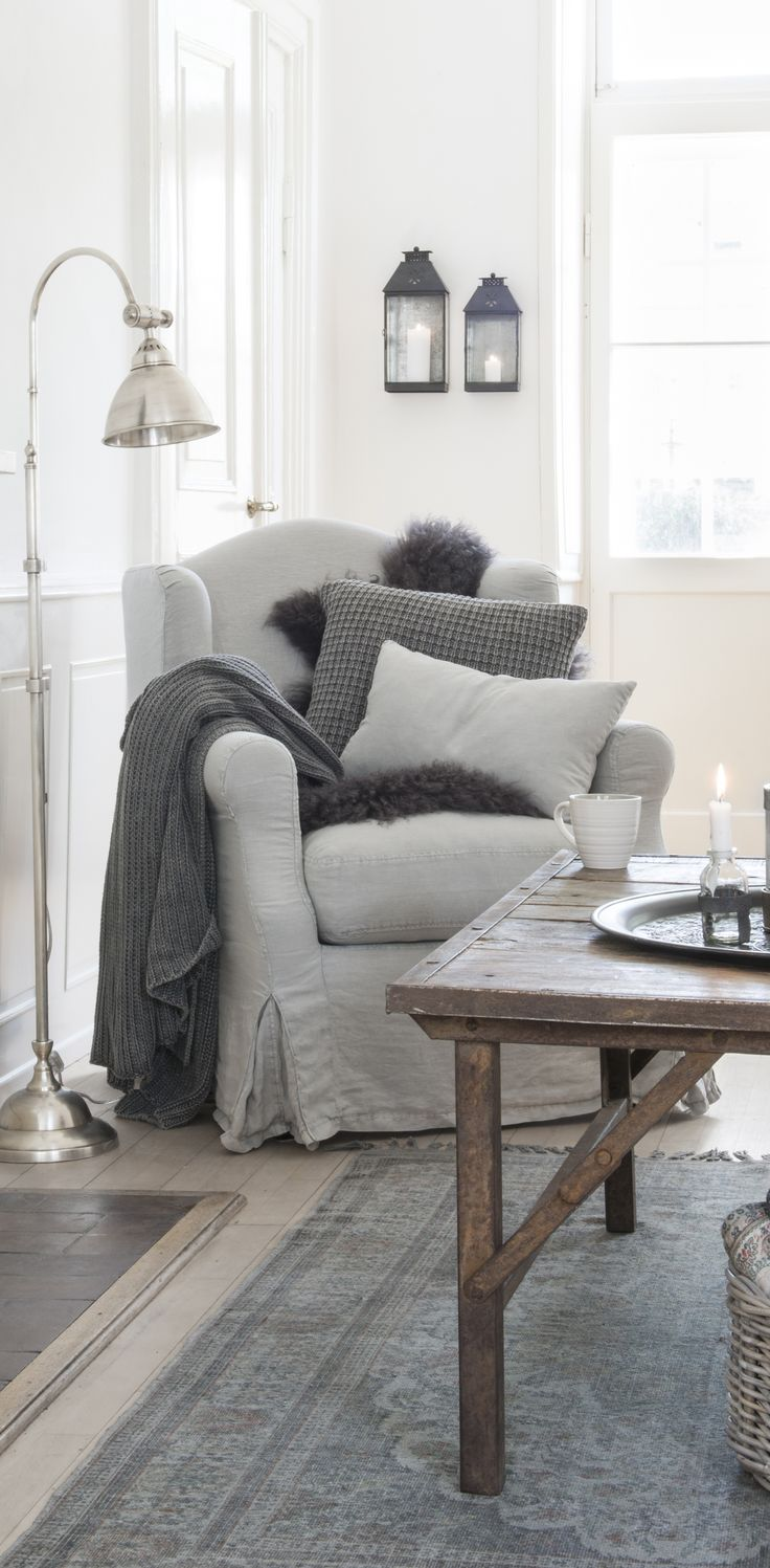 White sitting room with gray furniture, throw blankets, and pillows