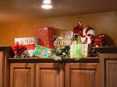 Use some of the presents to decorate above the cabinets and pull them down on Christmas.... good solution for sneaky kids!!