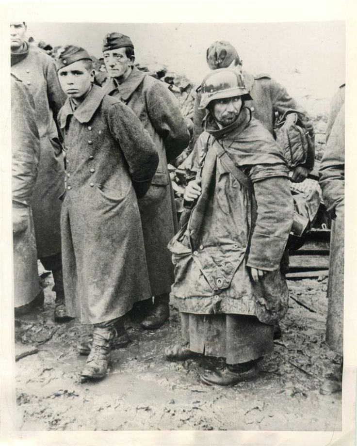 1944- Battle-weary Germans who were the last to surrender during the battle of Hurtgen Forest are shown awaiting transfer to prison camp near Jungersdorf, Germany.