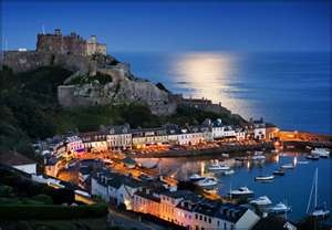 The rising moon lights the English Channel over this village on Jersey.