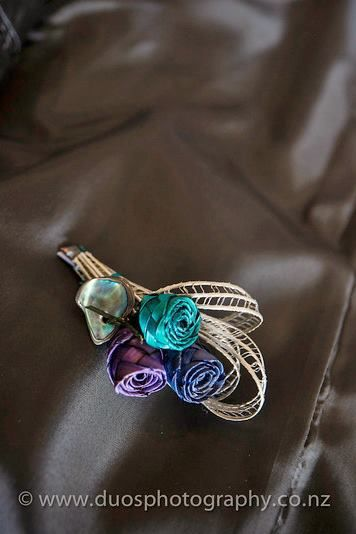 Three bud buttonhole with a paua piece. This is a smaller sized buttonhole that would suit a pageboy. www.flaxation.co.nz