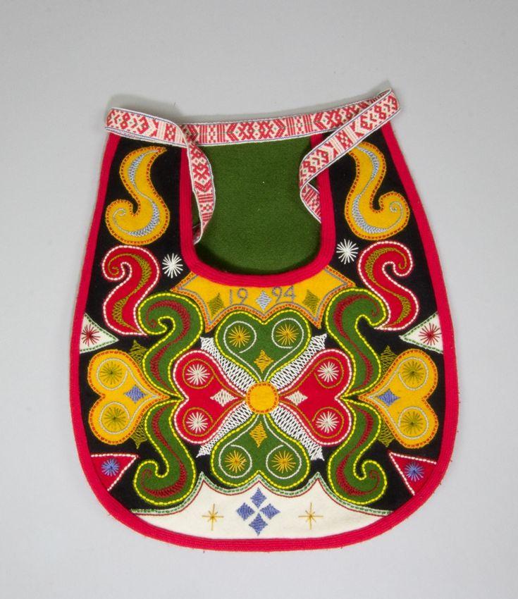 Kjolsäck till dräkt för kvinna från Leksands socken, Dalarna. Modell med u-formad öppning för handen. Tillverkad av svart ylletyg, kläde, med applikationer av kläde i rött, grönt, gult och vitt, hjärtformat motiv i mitten och s-formade figurer runtom. Broderier i flera färger både på och mellan applikationerna, ullgarn och bomullsgarn, läggsöm för att fästa ner applikationerna och dessutom flätsöm, stjälksöm och sticksöm. Under öppningen årtalet 1994 broderat med stjälksöm. Kantad med rött…