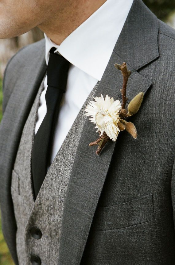 Adopt a more woodsy, warm theme for the groom's boutonniere, keeping flowers to a minimum and incorporating fall details like branches, glasses, acorns, and leaves.