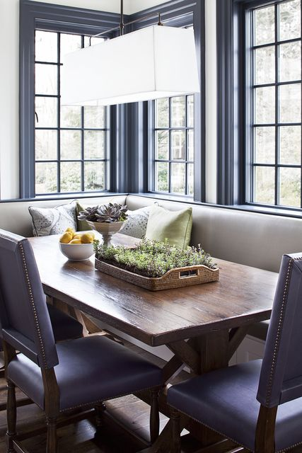 The breakfast nook continues to be a home's most important spot for family meals and good conversation. The banquette and chairs are upholstered in vinyl, providing essential durability. @alisbergparker. See the whole home: http://www.deringhall.com/daily-features/contributors/dering-hall/tour-a-modern-family-home-with-classic-roots